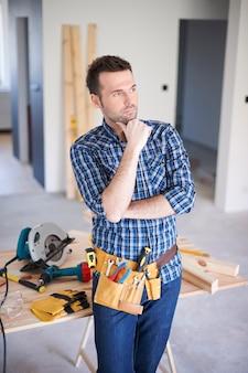 Carpinteiro trabalhando em uma casa e pensando