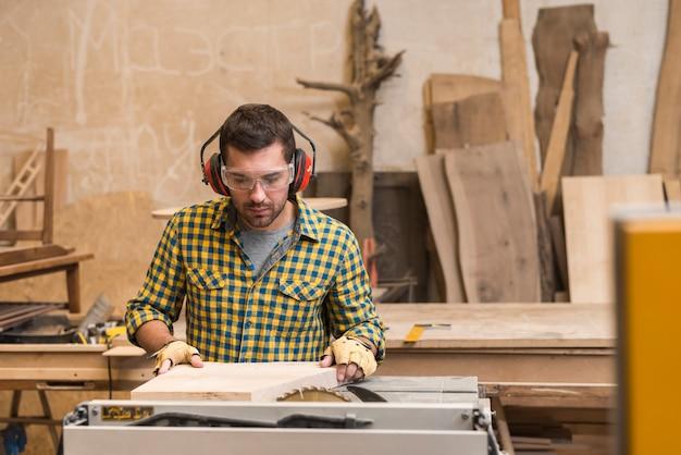 Carpinteiro trabalhando em uma serra elétrica cortando alguma placa