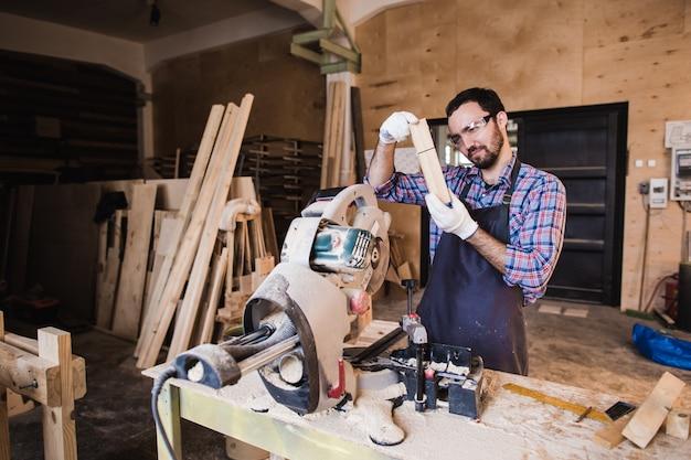 Carpinteiro trabalhando em uma serra elétrica cortando algumas tábuas, ele está usando óculos de segurança