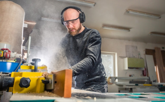Carpinteiro trabalhando em uma serra para carpintaria em uma oficina de carpintaria, conceito industrial