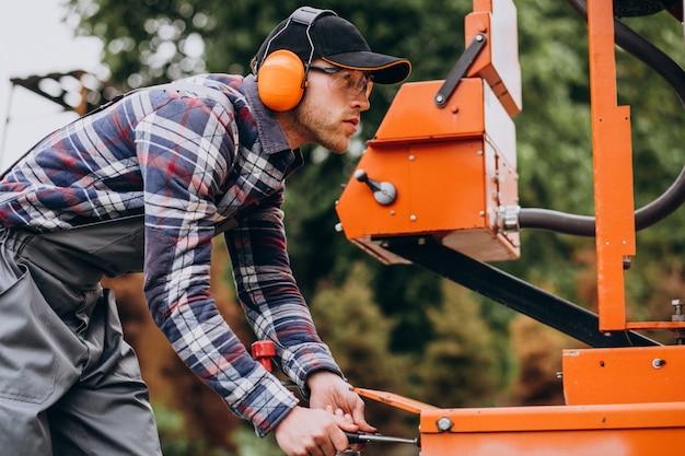 Carpinteiro trabalhando em uma serraria em uma fabricação de madeira