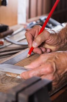 Carpinteiro trabalhando na bancada de trabalho, ferramentas de marcenaria e madeira