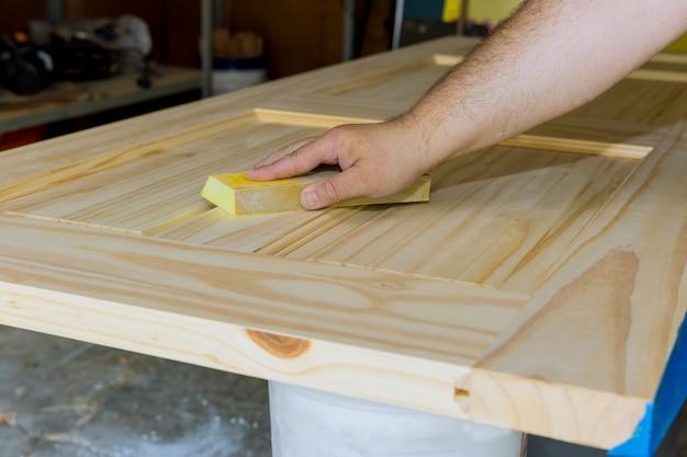 Carpinteiro trabalhando na lixa de trabalhador, com porta de madeira de bloco de lixar