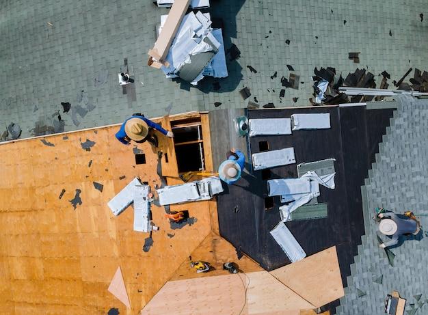 Carpinteiro trabalhando no telhado de telha de asfalto de substituição