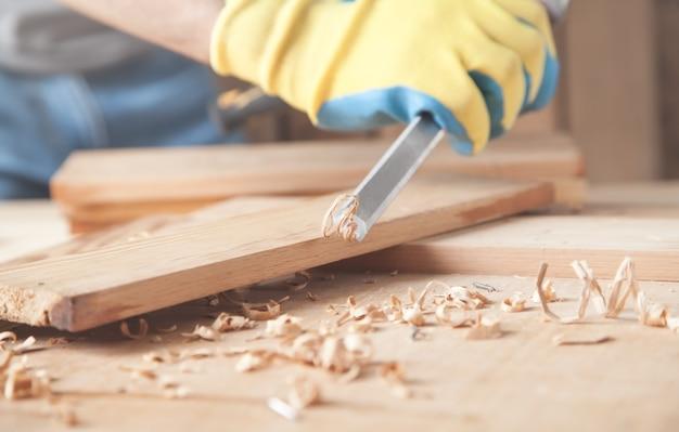 Carpinteiro usando formão em prancha de madeira.