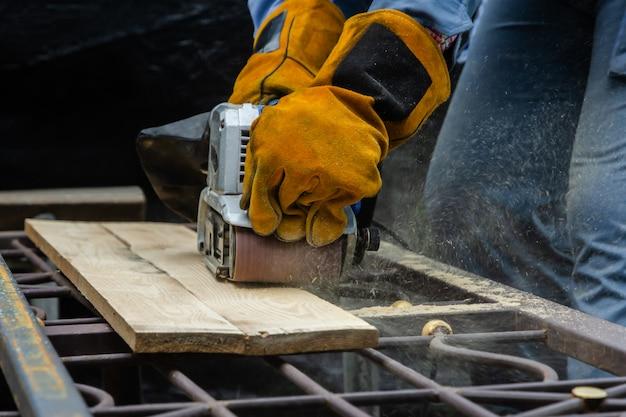 Carpinteiro usando luvas e lixar a placa de madeira com lixadeira de mão