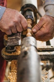 Carpinteiro usando madeira para fazer esculturas no ateliê