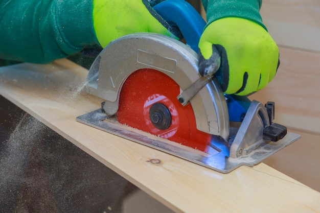 Carpinteiro usando serra circular manual para cortar tábuas de madeira com ferramentas elétricas em uma serraria para trabalhar madeira.