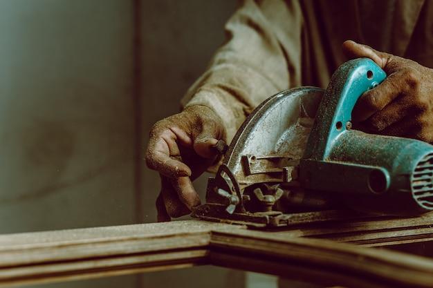 Carpinteiro usando serra circular para cortar tábuas de madeira