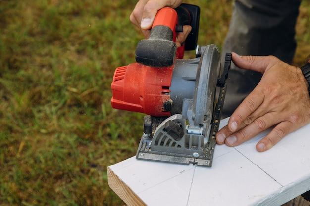 Carpinteiro usando serra circular para vigas de madeira