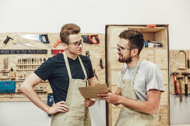 Carpinteiros com documentos olhando uns aos outros