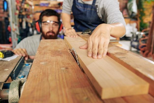 Carpinteiros cortando prancha de madeira