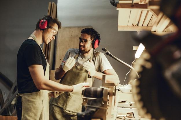 Carpinteiros jovens falando perto da bancada