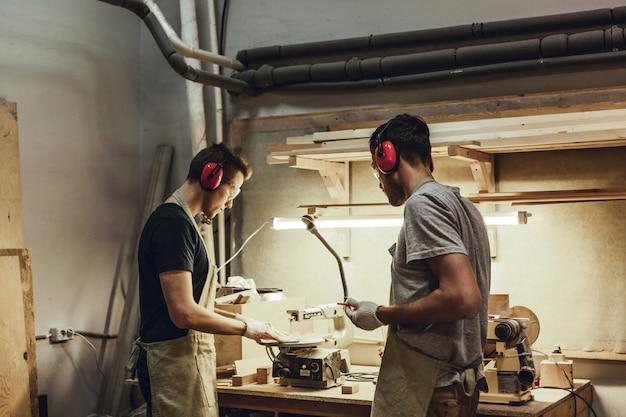 Carpinteiros jovens usando quebra-cabeças de mesa