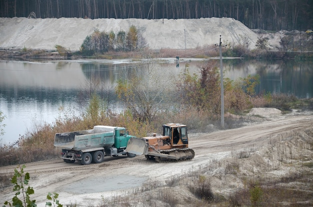 Carregadeira caterpillar e caminhão basculante trabalham na pedreira de mineração a céu aberto
