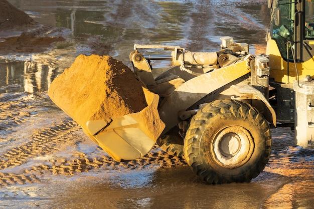 Carregadeira de rodas dianteiras de trator com areia no balde de terraplenagem funciona no conceito de canteiro de obras