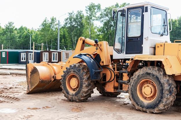 Carregadeira de rodas pesadas com uma caçamba em um canteiro de obras. equipamentos para terraplenagem, transporte e carregamento de materiais a granel - terra, areia, brita.