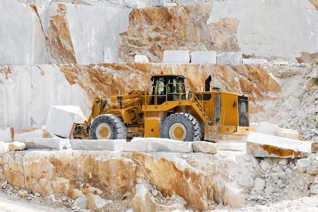 Carregadeira frontal pesada transportando mármore em uma pedreira a céu aberto ou mina em carrara, toscana, itália, durante a extração da rocha de uma montanha