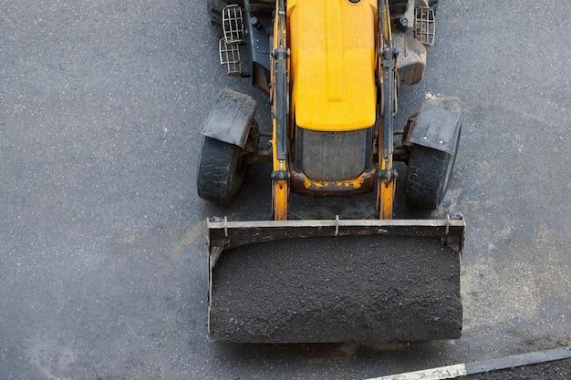 Carregador com solo em pás. reparação de estradas ou relvados pelo município. trator trabalhando canteiro de obras. vista do topo.