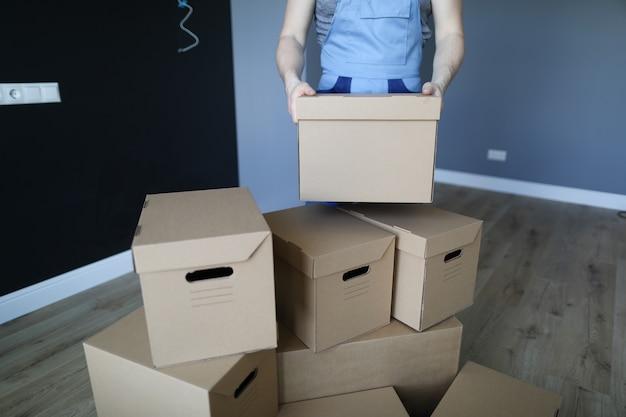 Carregador empilha caixas de papelão em uma sala vazia
