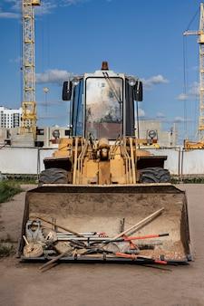 Carregador frontal pesado em um canteiro de obras com uma ferramenta de construção na caçamba. equipamentos para terraplenagem, transporte e carregamento de materiais a granel - terra, areia, brita.