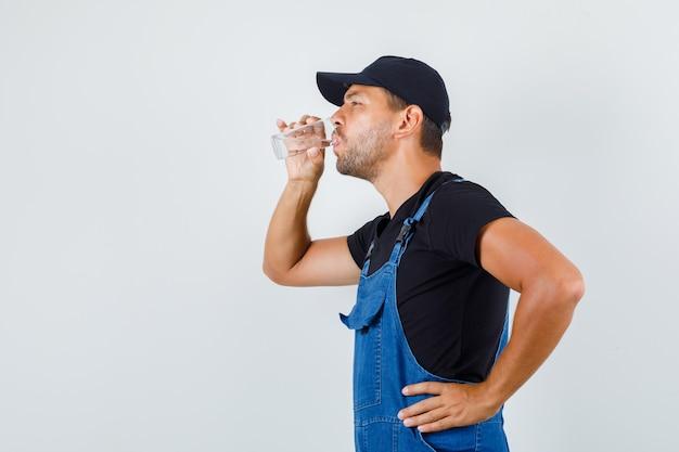 Carregador jovem bebendo água e sentindo calor de uniforme.