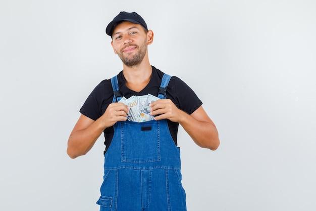 Carregador jovem colocando dinheiro no bolso de uniforme e olhando alegre, vista frontal.