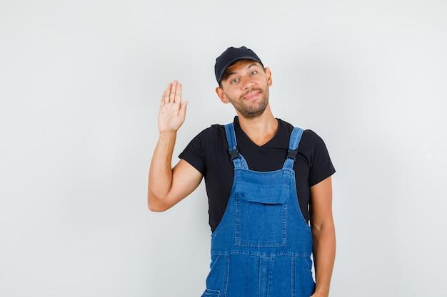 Carregador jovem de uniforme acenando com a mão para se despedir e parecendo feliz, vista frontal.