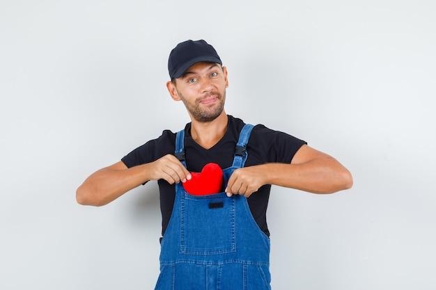 Carregador jovem de uniforme, colocando um coração vermelho no bolso e olhando alegre, vista frontal.
