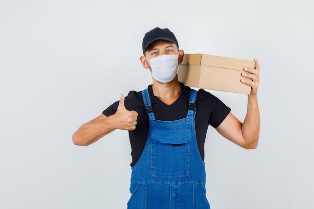 Carregador jovem de uniforme, máscara segurando a caixa de papelão com o polegar para cima, vista frontal.