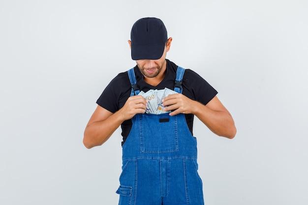 Carregador jovem de uniforme tirando dinheiro do bolso e olhando cuidadoso, vista frontal.