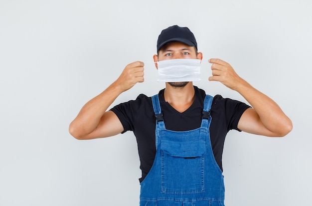 Carregador jovem segurando máscara médica sobre a boca em vista frontal uniforme.