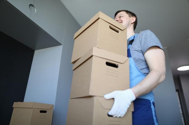 Carregador masculino carrega caixas de papelão vazias dentro de casa