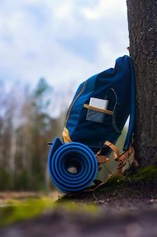 Carregador portátil de viagem. power bank carrega smartphone contra um pano de fundo de bolsas de viagem e floresta. conceito sobre o tema do turismo.