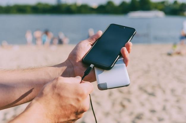 Carregador portátil nas mãos de um homem no espaço da praia. powerbank carrega o telefone.