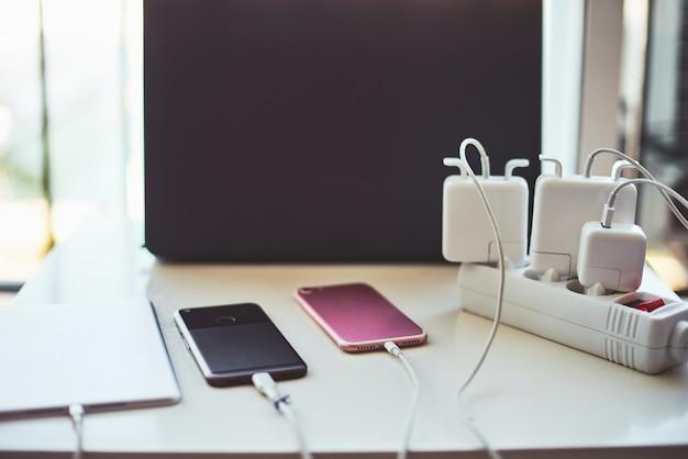 Carregadores de telefone e laptop na mesa