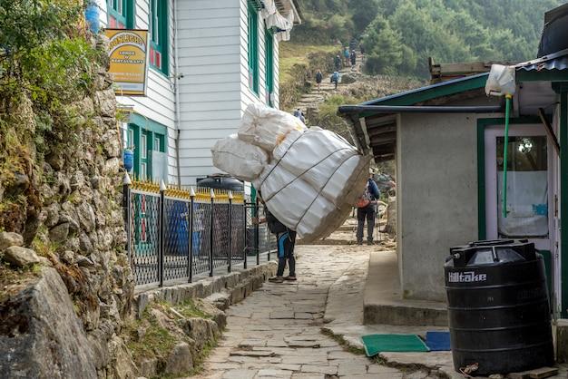 Carregadores sherpa transportando sacos pesados no himalaia no everest base camp trek, nepal.