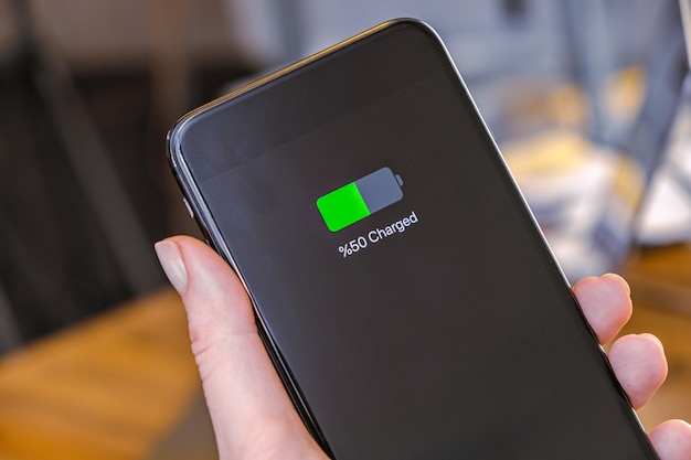 Carregamento da bateria da tela do smartphone mostrando a metade da bateria carregada na mão da mulher