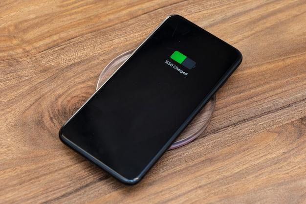 Carregamento da bateria do smartphone mostrando a bateria meio carregada no conceito de carregador sem fio rápido