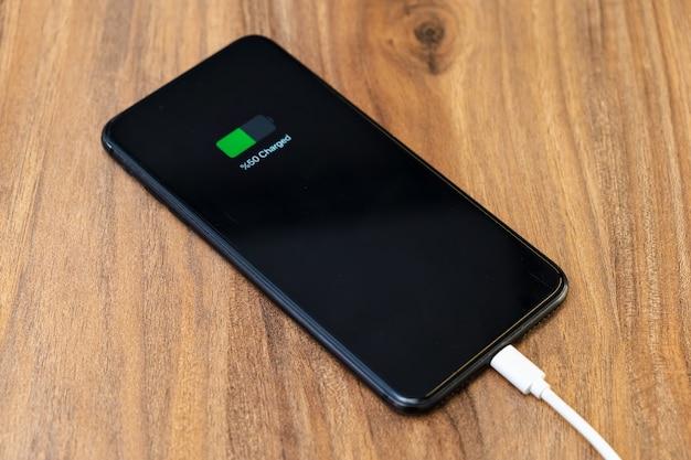 Carregamento de bateria de smartphone mostrando bateria meio carregada no conceito de carregador de cabo rápido