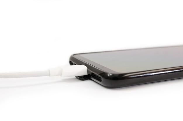 Carregamento de smartphone via cabo usb e fonte de alimentação em um fundo branco. carregamento com fio. Foto Premium