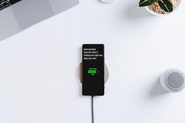 Carregamento de telefone inteligente no fundo branco da mesa do carregador sem fio