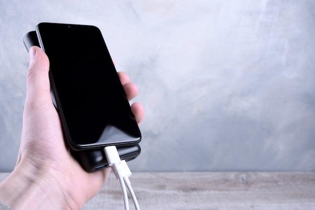 Carregamento do telefone, powerbank cobra smartphone, celular com banco de energia. profundidade de campo no banco de potência homem detém nas mãos