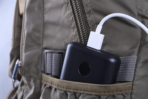 Carregamento do telefone, powerbank cobra smartphone, celular com banco de energia. profundidade de campo no banco de potência na mochila