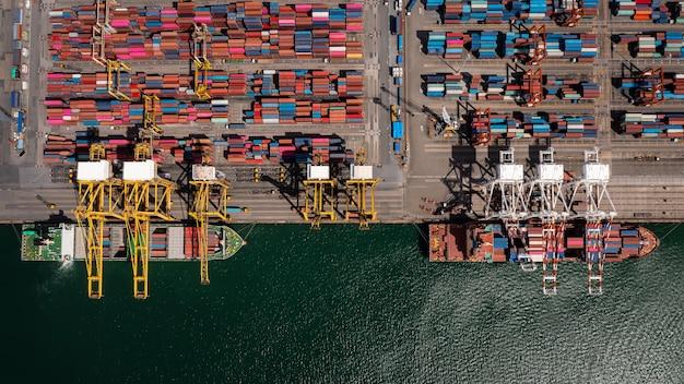 Carregamento e descarregamento de navios porta-contêineres em porto de alto mar, vista aérea de topo, serviços de negócios e logística de comércio comercial, importação e exportação, transporte de frete internacional em mar aberto em todo o mundo