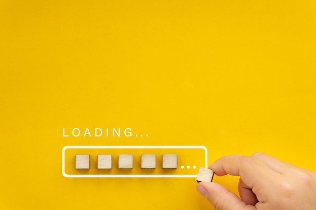 Carregando a mão colocando o cubo de madeira na barra de progresso carregando a barra no fundo amarelo brilhante