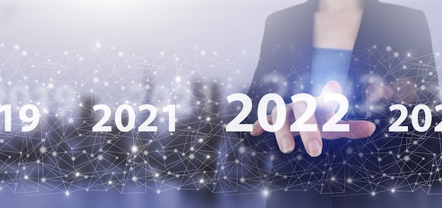 Carregando ano de 2021 a 2022. conceito inicial. holograma de tela digital de toque de mão 2022 cadastre-se no fundo desfocado luz da cidade. ano novo 2022, objetivo, plano, ação.
