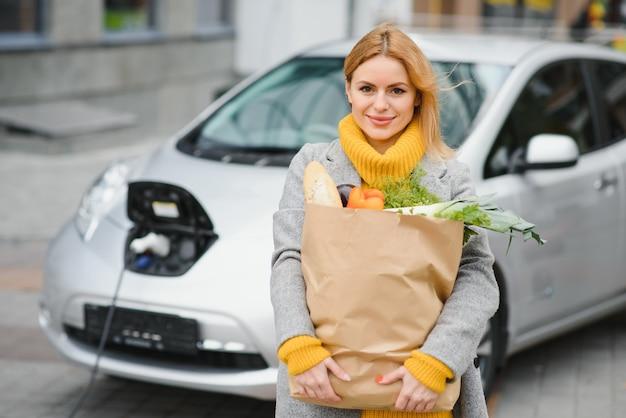 Carregando carro elétrico no posto de gasolina elétrico. mulher em pé perto do carro.