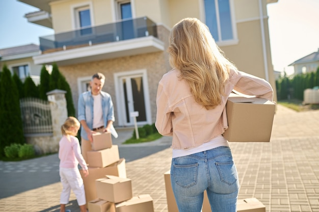 Carregando, coisas. mulher com cabelo loiro comprido com baú de costas para a câmera caminhando em direção a marido e filha perto de casa nova
