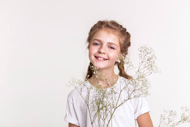Carregando flor do campo. senhora alegre em uma camiseta branca posando ativamente com flores brancas espessas nas mãos